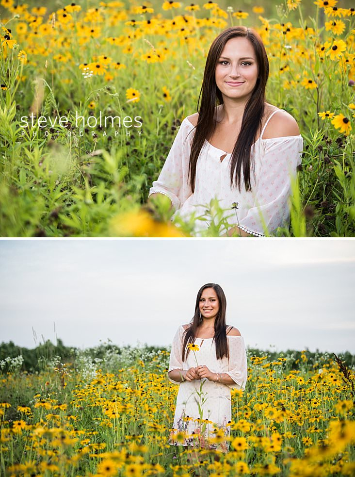 22_Young woman wearing white dress smiles for senior portrait in field of wildflowers.jpg