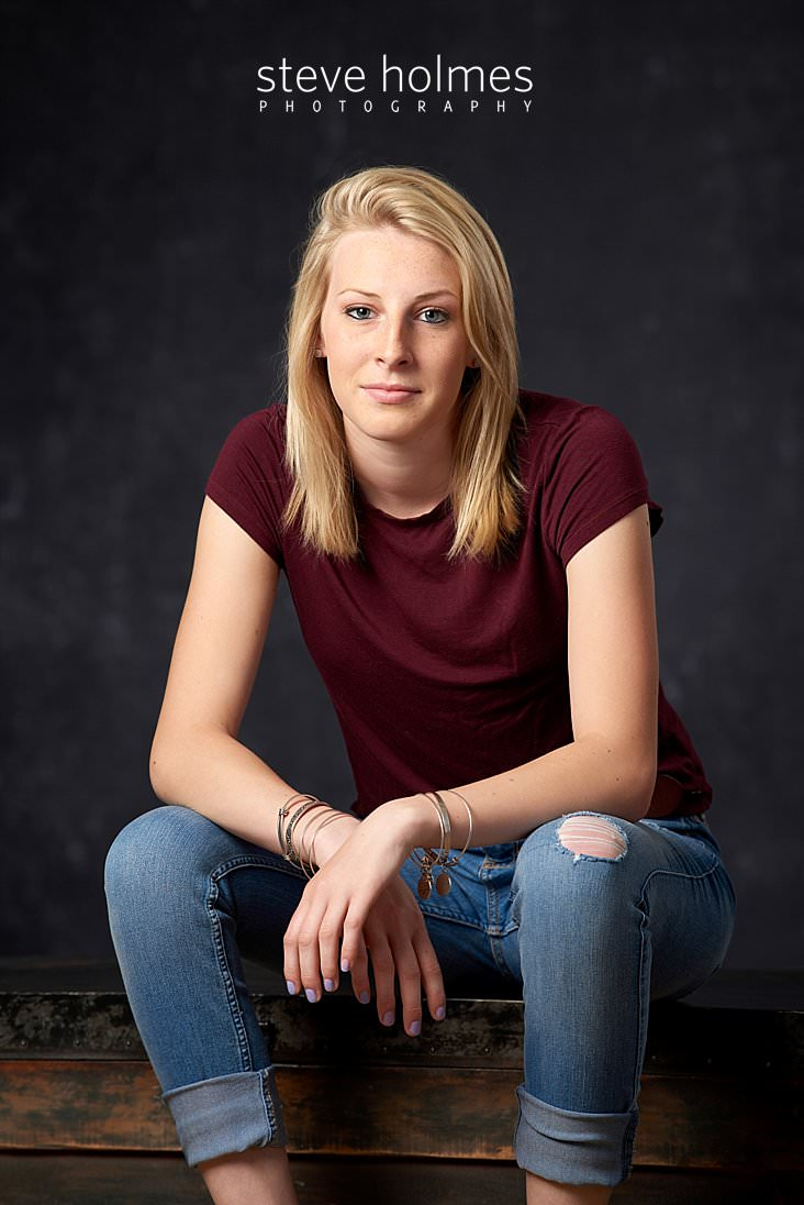 01_Blonde teen girl poses for studio senior portrait wearing jeans and a red tee shirt.jpg