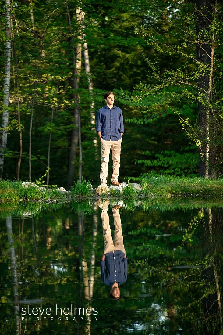 01_Young man stands on stones next to pond for senior photo.jpg