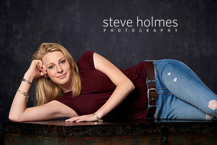 02_Blonde teenaged woman poses laying down in studio for senior portrait wearing jeans and red teeshirt.jpg