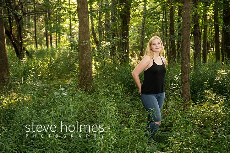 04_Teen in black tank top and ripped jeans poses with her hands in her back pockets in the summer forest for outdoor senior photo.jpg