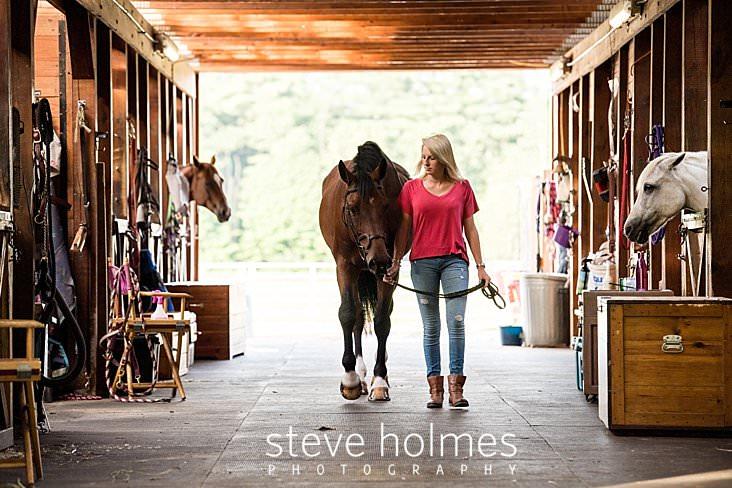 06_Teen girl looks at her horse as she leads it through barn for senior portrait.jpg