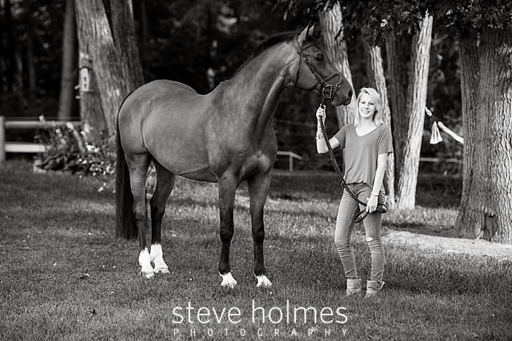 07_Black and white senior portrait of young woman and her horse under trees.jpg