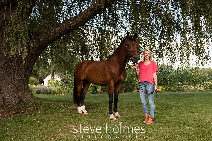 12_Blonde teen stands under a tree with her horse for senior photo.jpg