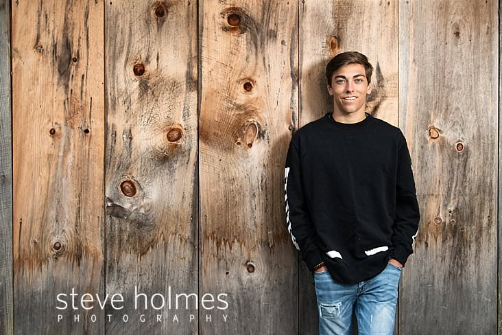 12_Teen boy in black and white sweatshirt and jeans poses in front of a barn wall for senior photo.jpg