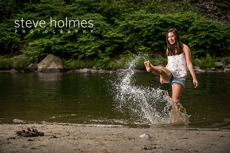 13_Smiling teen kicks water on the banks of a river in outdoor senior portrait.jpg
