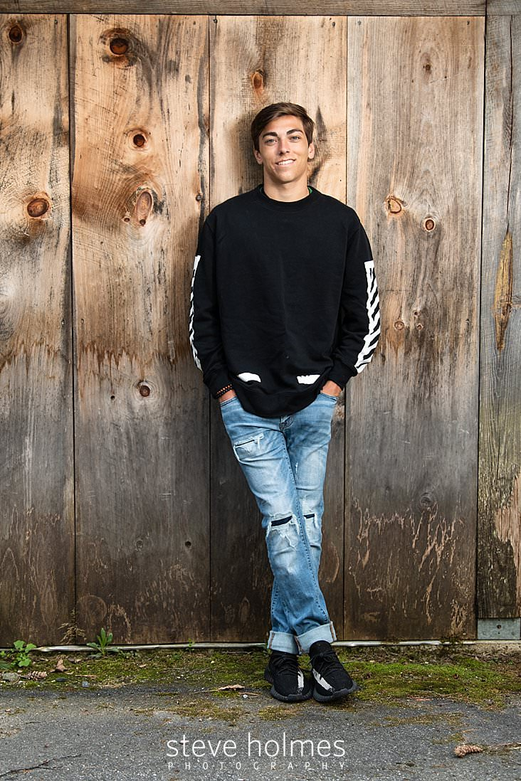 13_Teen boy in black and white sweatshirt and jeans poses with his legs crossed casually in front of barn wall for senior photo.jpg