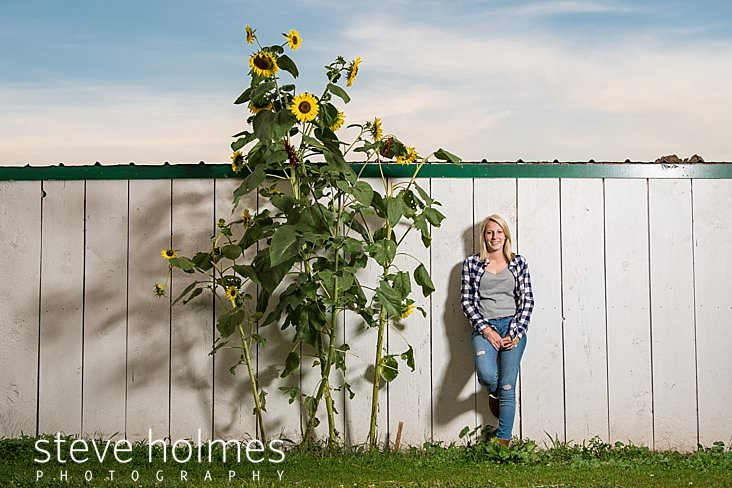 13_Teen leans against white barn wall next to sunflowers for senior portrait.jpg