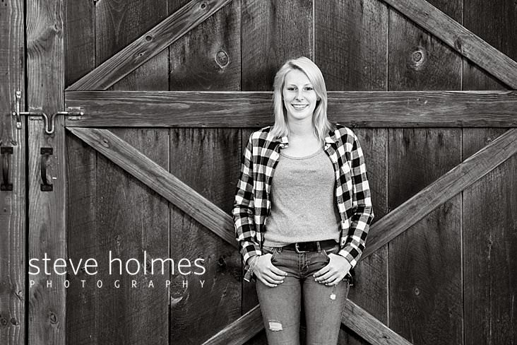 14_Black and white senior portrait of young woman wearing plaid shirt leaning against barn.jpg