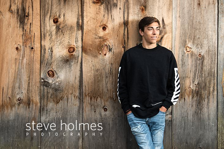 14_Young man wearing black and white sweatshirt and jeans poses with his hands in his pockets against barn wall for senior portrait.jpg