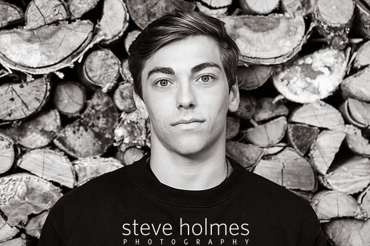 15_Black and white senior portrait of a young man against a woodpile.jpg
