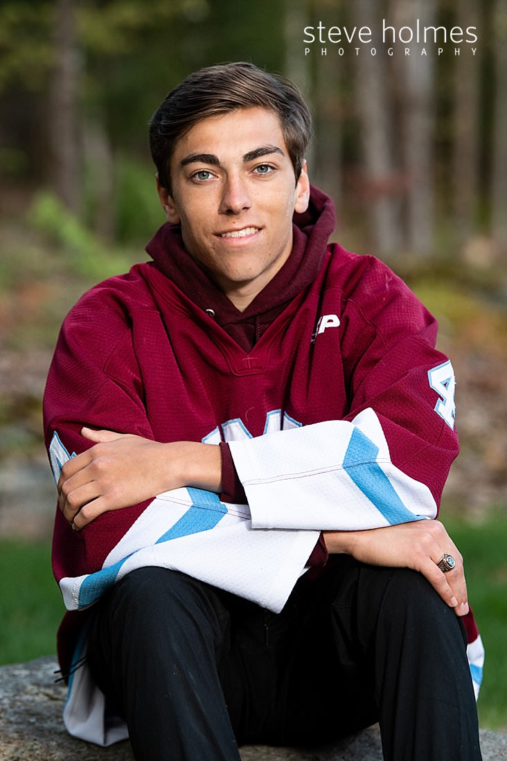 19_Teen boy sits outside wearing his hockey jersey for senior portrait.jpg