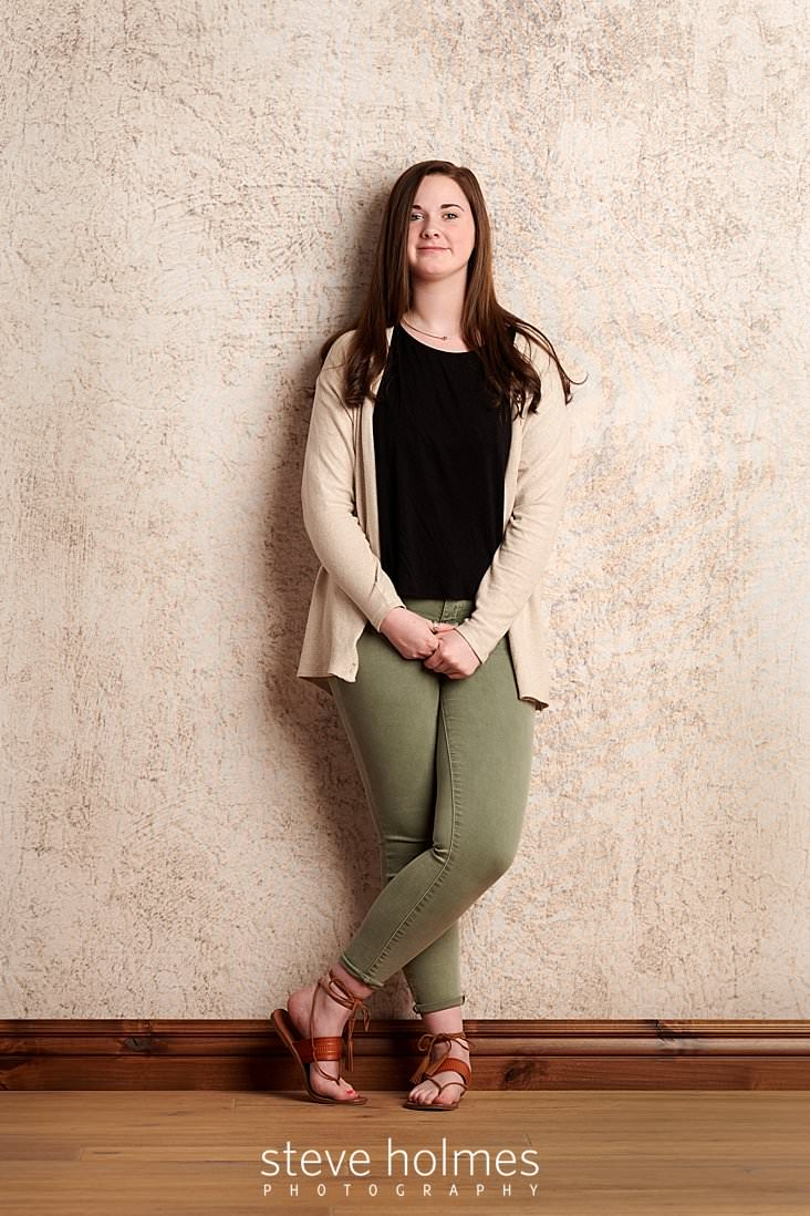 02_Brunette teen wearing jeans and tan sweater leans against wall for studio senior portrait.jpg