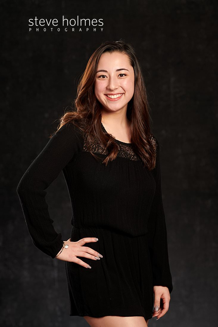 04_Senior portrait in studio with young woman in black dress standing with hand on her hip.jpg