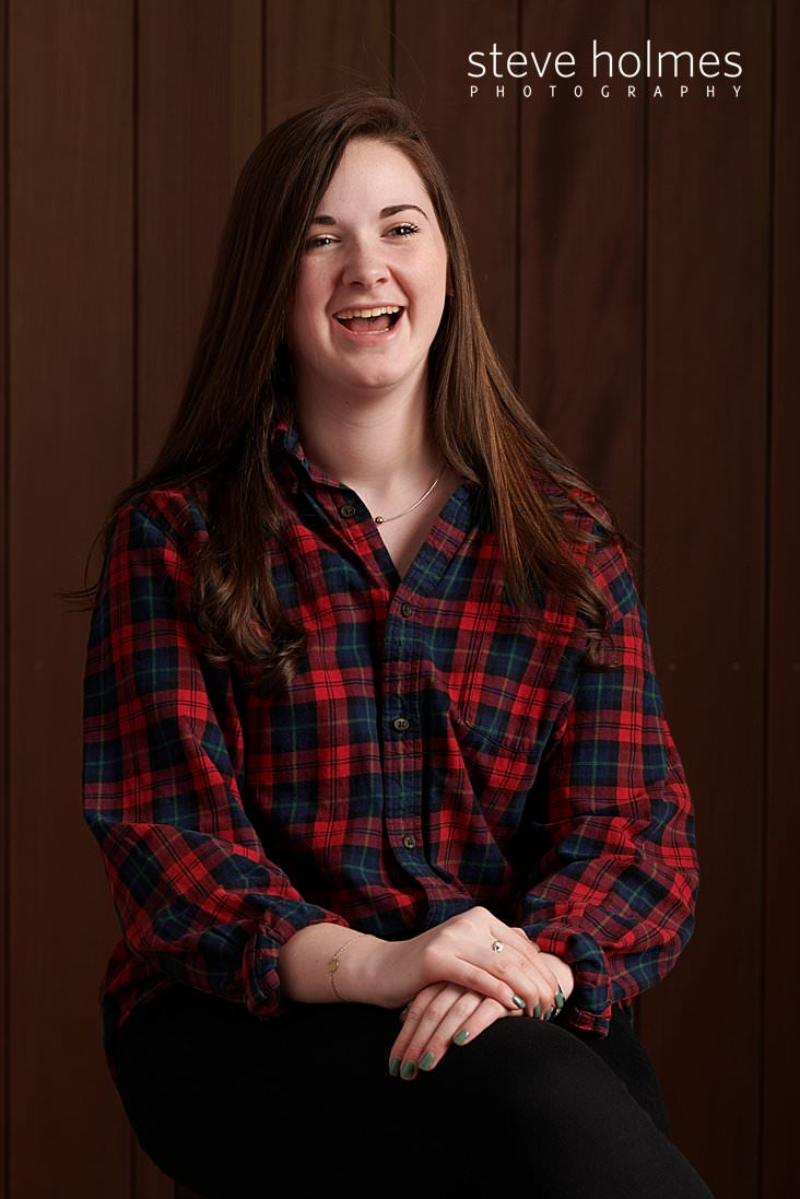 04_Teen girl in plaid shirt laughs with arms crossed on knee for studio senior portrait.jpg