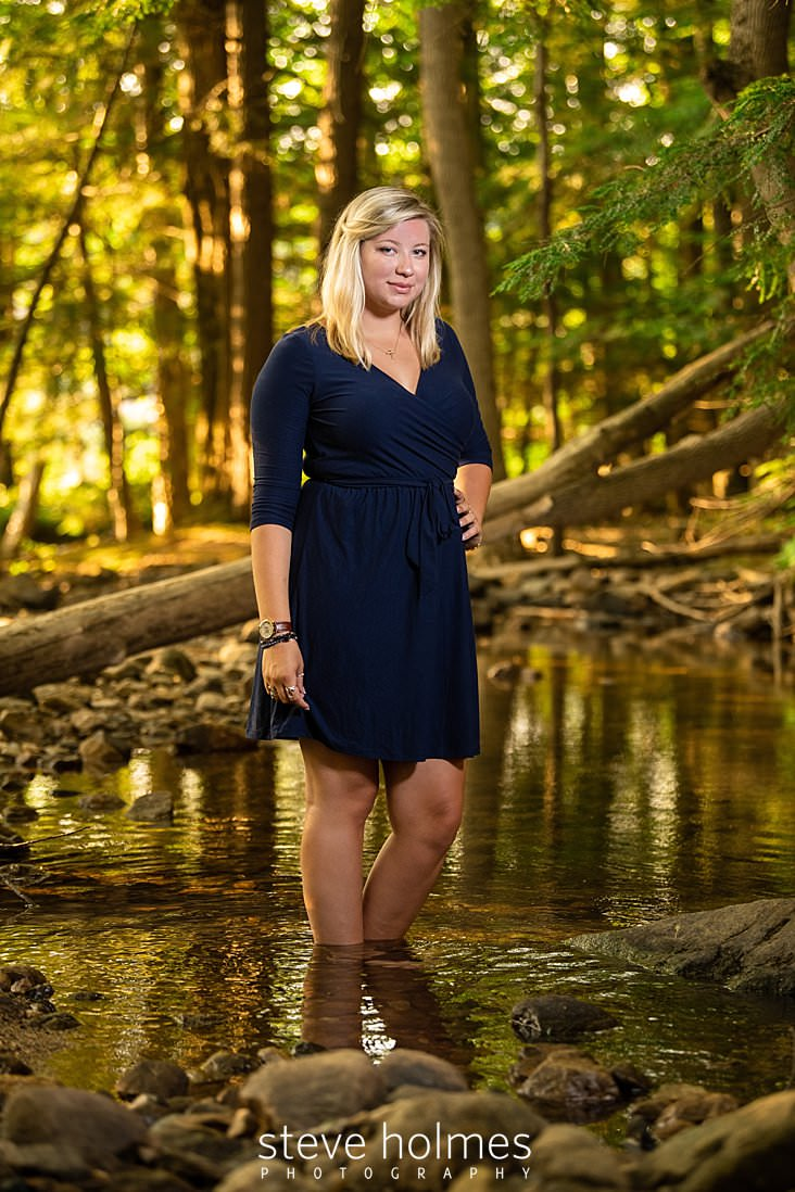05_Blonde teenaged girl in blue wrap dress wades in stream for outdoor senior photo_.jpg