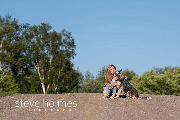 05_Teen girl kneels on crest of hill with her dog for senior portrait.jpg