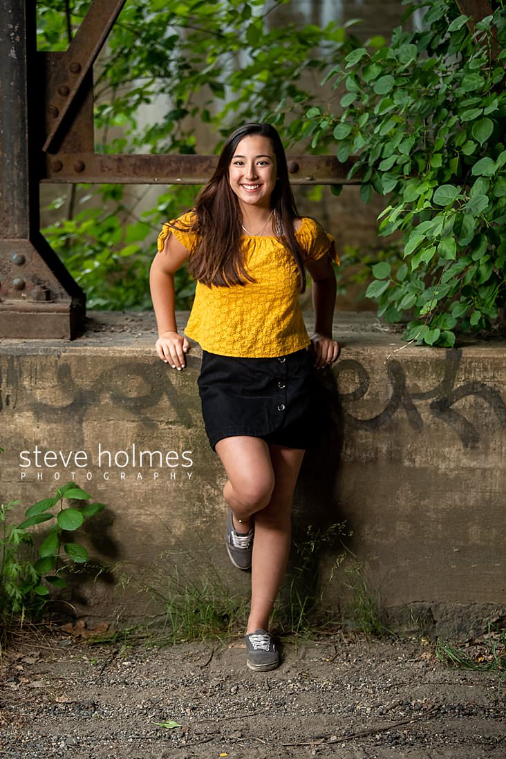 06_Teen girl leans against industrial bridge structure wearing yellow top and black skirt for outdoor senior photo.jpg