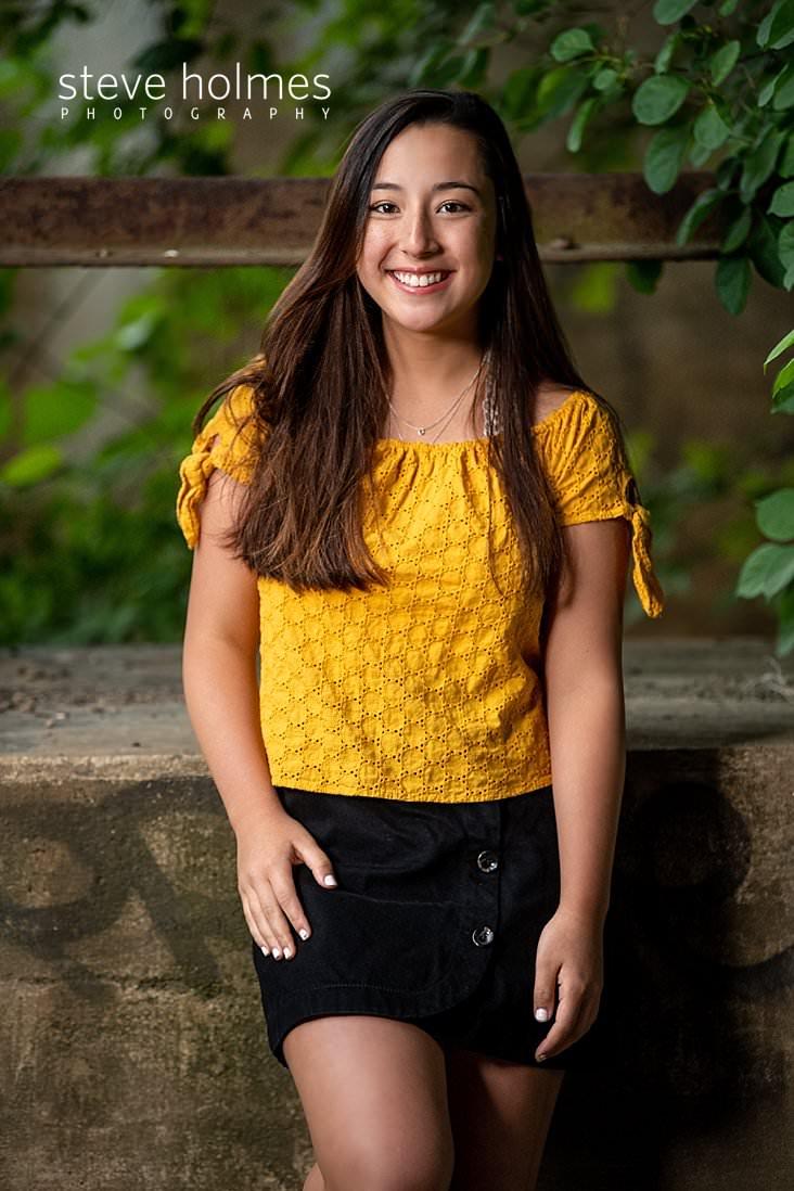 07_Teenaged girl in yellow top and black skirt smiles for outdoor senior portrait.jpg