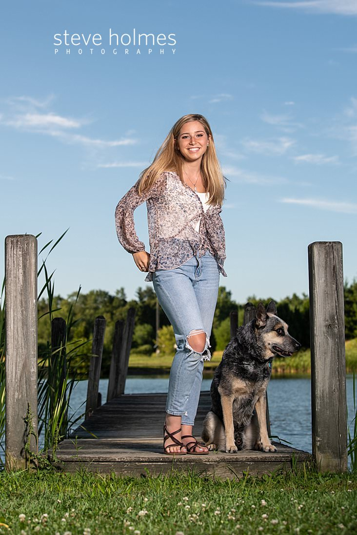 08_Teen poses on dock with her dog for outdoor senior portrait next to pond.jpg