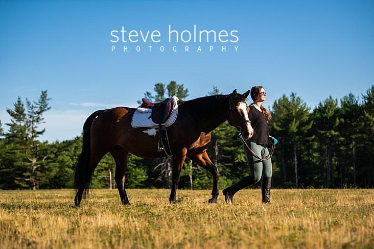 10_Teen girl leads her horse through field for senior portrait.jpg