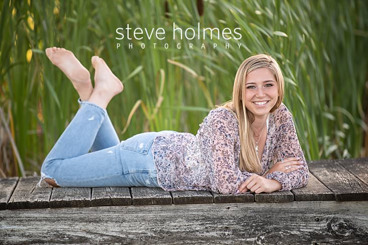 11_Blonde teen wearing jeans and a patterned blouse lays on a dock and poses for senior portrait.jpg