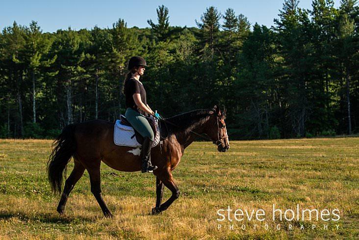 11_Teen girl rides her horse through field for senior portrait.jpg