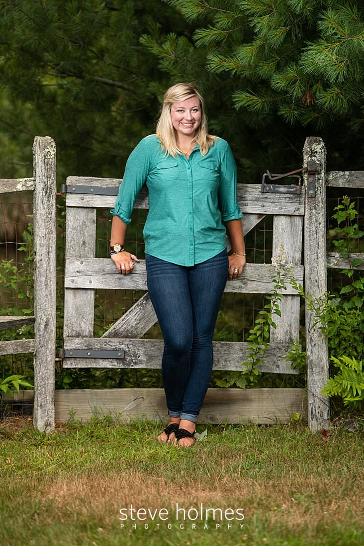 13_Blonde teen leans against wooden gate for outdoor senior photo.jpg