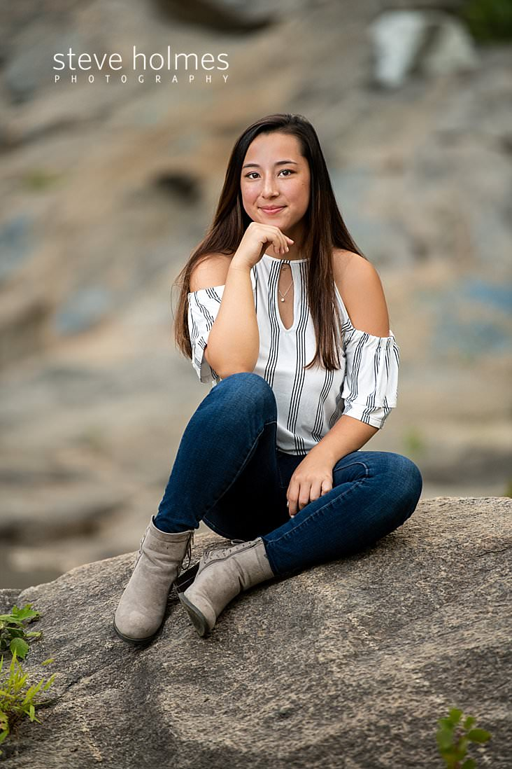 14_Teen in jeans and an off the shoulder striped top sits on a rock for senior portrait.jpg