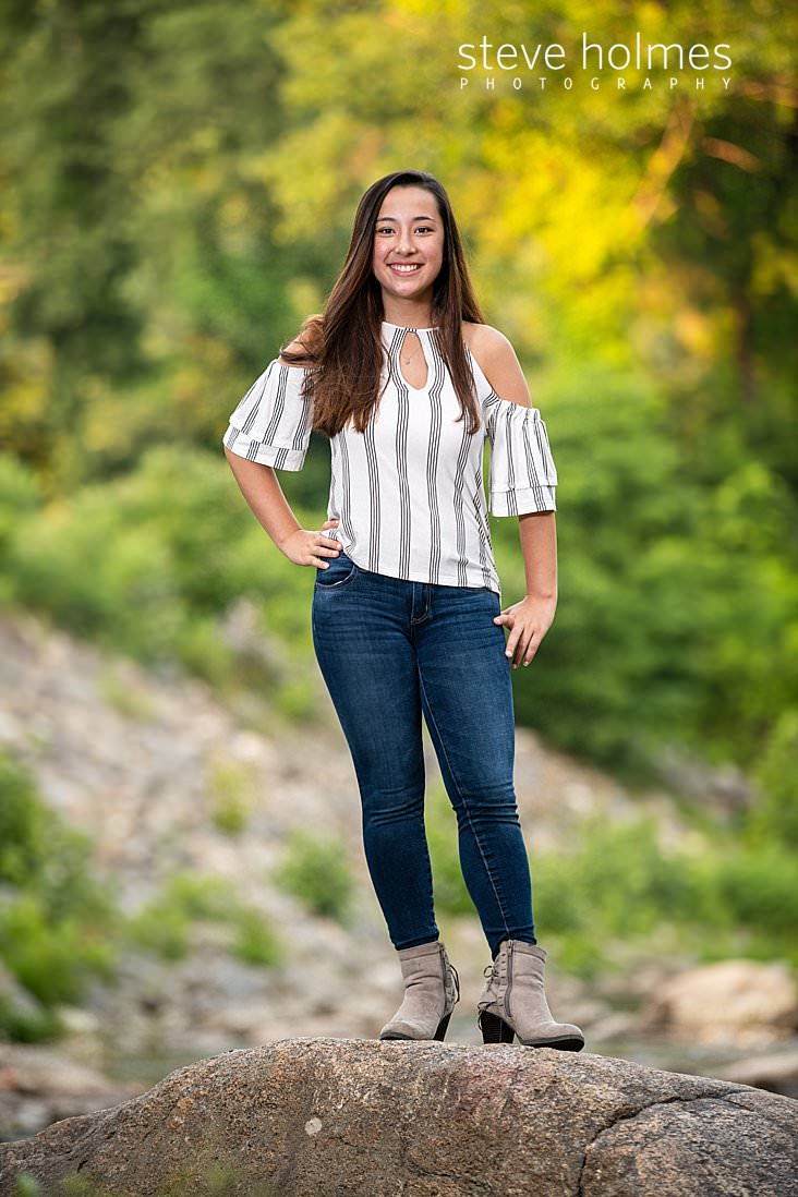 15_Teen in jeans and an off the shoulder striped top stands on a rock for outdoor senior portrait.jpg