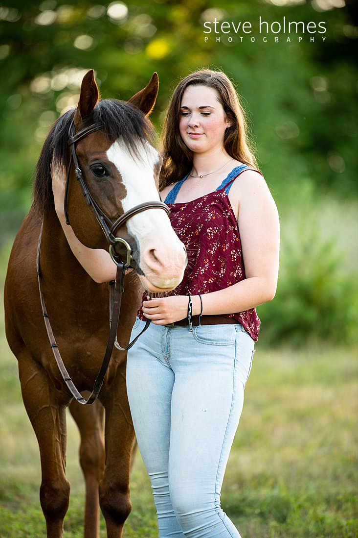 16_Brunette teen pets her horse for outdoor senior portrait.jpg