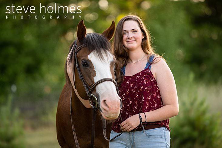 17_Brunette teen smiles for outdoor senior portrait while petting horse.jpg