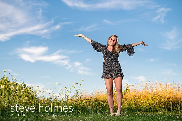 17_Teen in floral short romper puts her arms in the air for late afternoon outdoor senior portrait in field.jpg