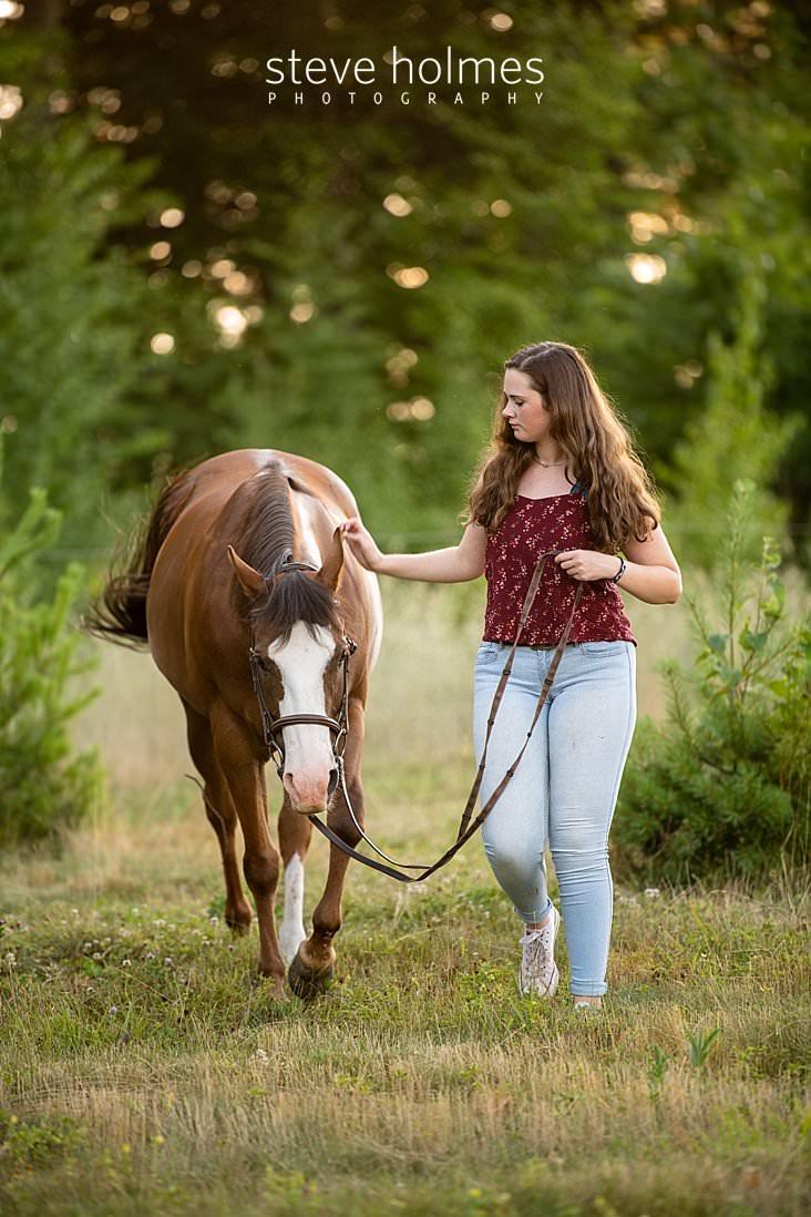 18_Brunette teen walks with horse in field for senior photo.jpg