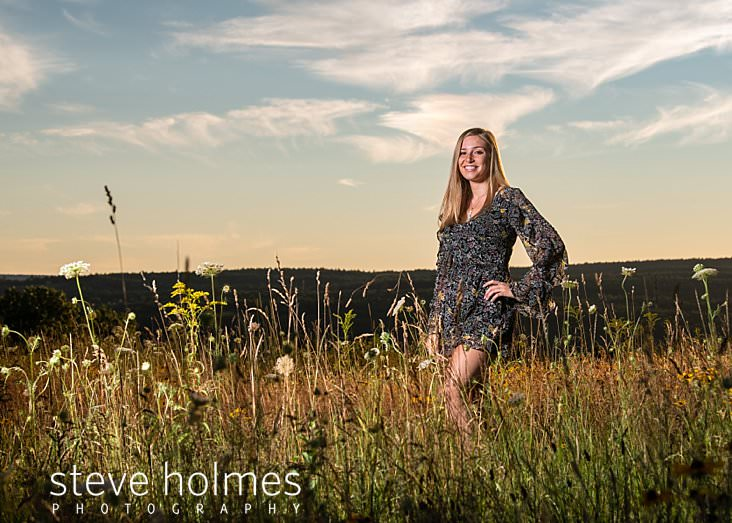 18_Teen wearing floral romper stands in field at sunset for senior photo.jpg