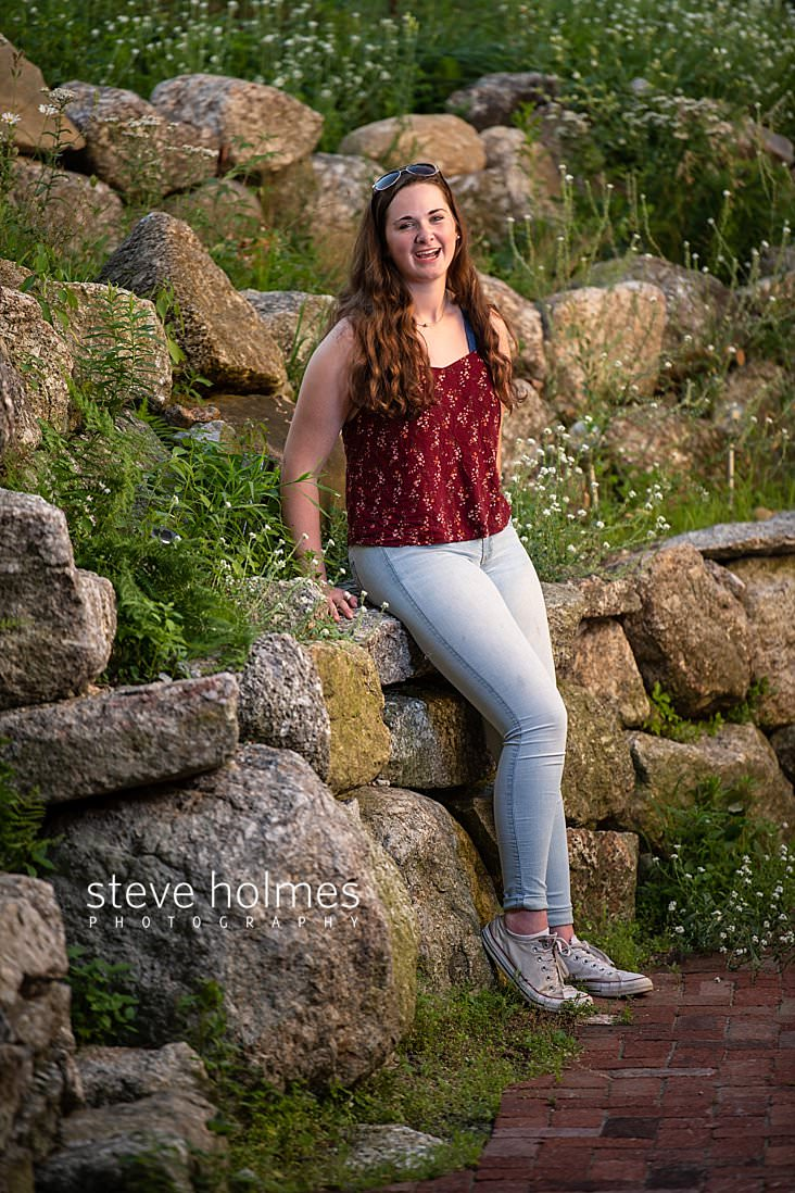 20_Brunette teen in jeans and a red floral tank top leans against stone wall for senior portrait.jpg