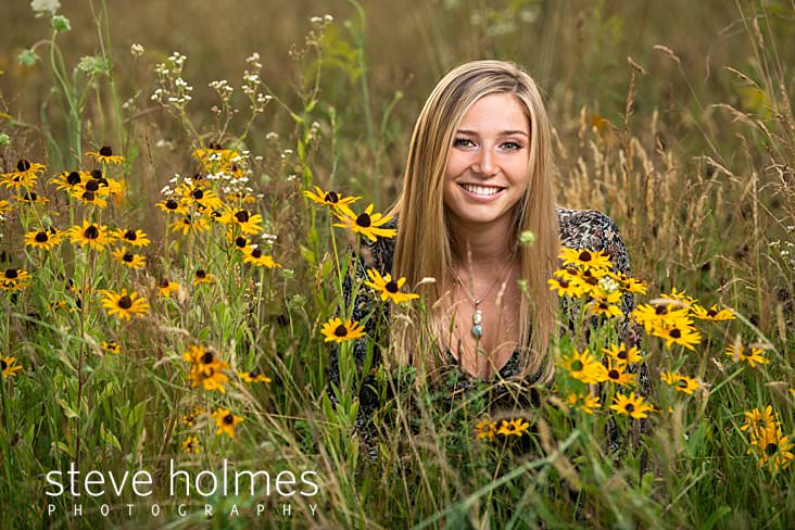 21_Blonde teen sits in field of wildflowers smiling for senior portrait.jpg