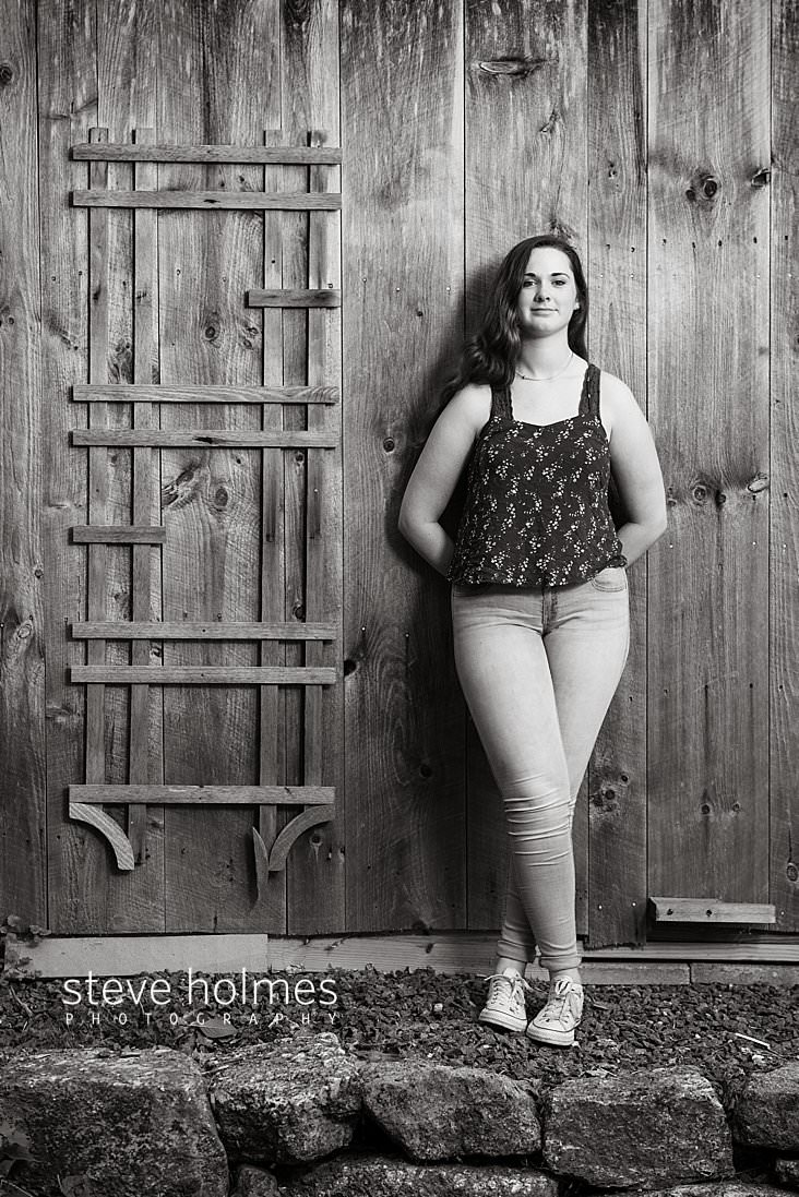 22_Brunette teen leans against a barn wall wearing jeans and a tank top for black and white senior portrait.jpg