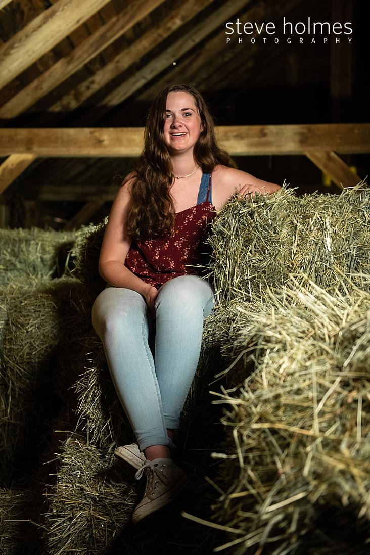 25_Teen girl sits on a pile of hay bales in barn for senior portrait.jpg