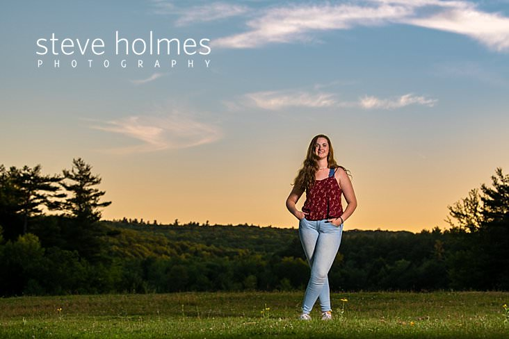 26_Teen girl stands in field at sunset with her hands in her jean pockets for senior portrait.jpg