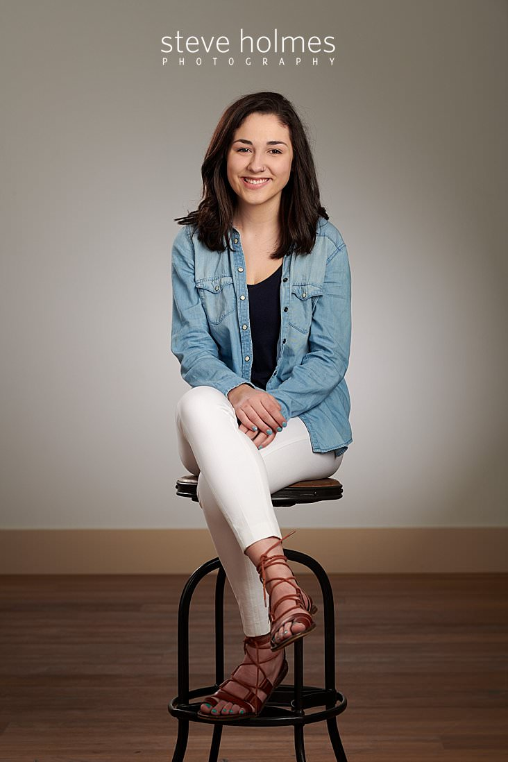 01_Brunette teen in jean shirt and white pants sits on a stool in studio senior portrait.jpg