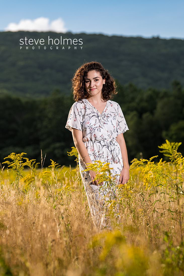07_Curly haired brunette in wrap dress smiles for senior photo in New England field.jpg