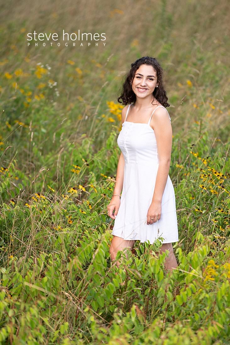 13_Teen in white dress stands in a field for senior portrait.jpg