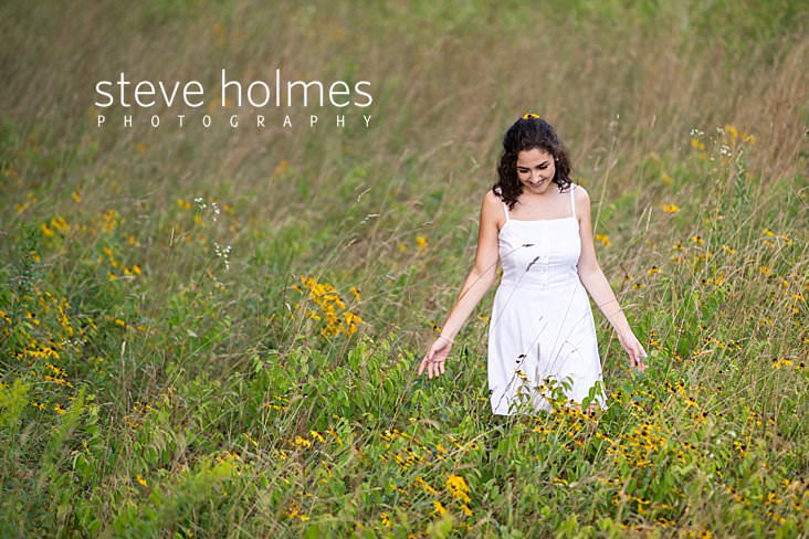 15_Laughing teen walks through field of flowers for senior portrait.jpg