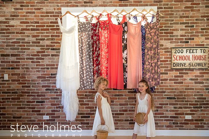 20_Flower girls play in front of wedding gown and bridesmaids dresses.jpg