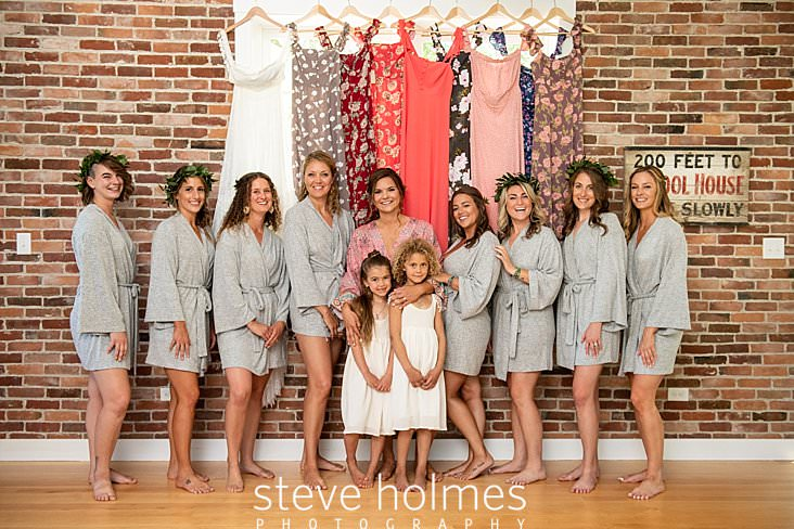 22_Bride, bridesmaids and flower girls pose in front of hanging dresses before wedding.jpg