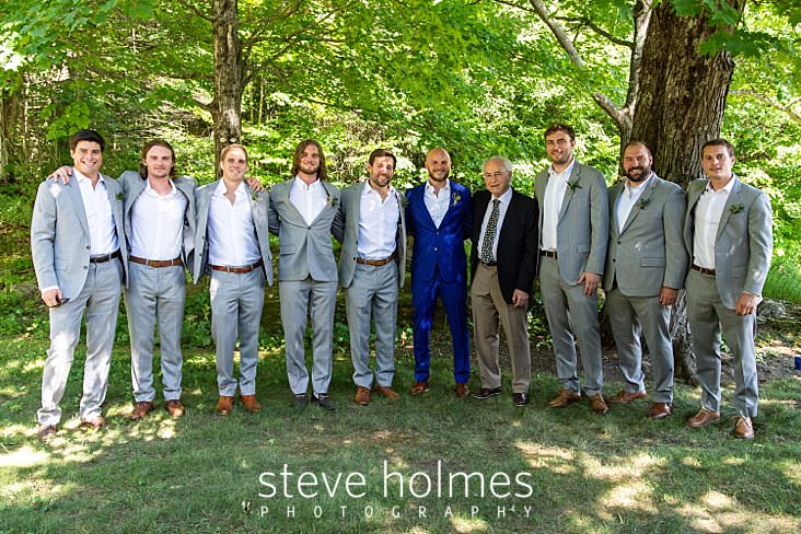 23_Groom in blue suit stands with his father and groomsmen in grey suits outside_.jpg