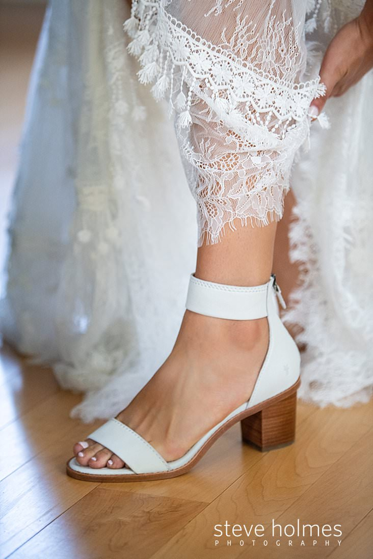 24_Bride puts on her white heels before ceremony.jpg
