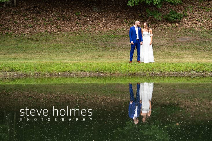 34_Bride and groom stand near pond and are reflected in water.jpg