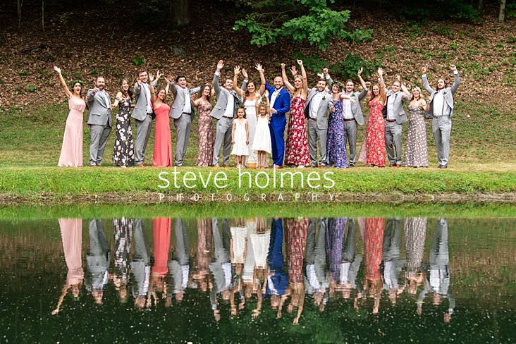 36_Bridal party stands on the banks of pond with their arms raised.jpg
